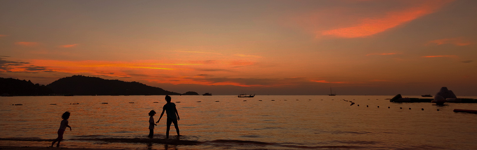Phuket, Thailand - March 16, 2011 : Mother and children enjoying the beuatiful sunset at Patong Beach in Phuket